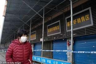 uomo con mascherina vicino al mercato del pesce di wuhan