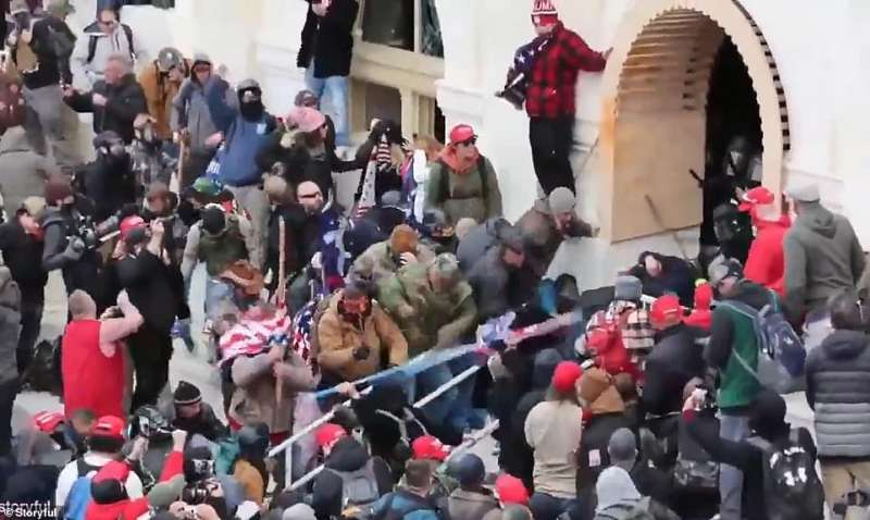 manifestanti picchiano un poliziotto con una bandiera americana a washington