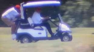 donald trump sulla golf car con il caddy aggrappato sul retro