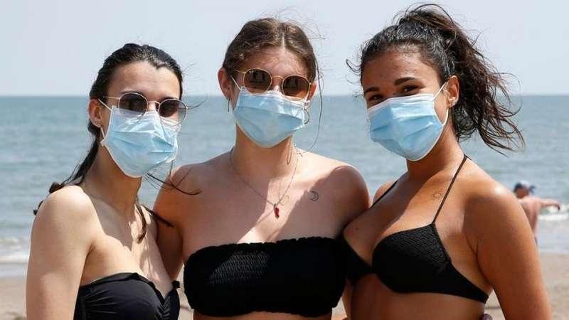 tre ragazze in spiaggia con la mascherina