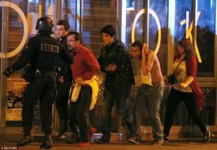 un agente aiuta a evacuare i sopravvissuti tra cui un uomo ferito alla testa